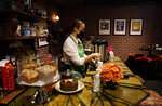 """Sara Olson makes coffee for visitors to the """"Friends""""-inspired """"Central Perk Cafe"""" during the Warner Bros. Studio Tour Hollywood media preview on June 24, 2021, in Burbank, Calif. (AP Photo/Chris Pizzello)"""