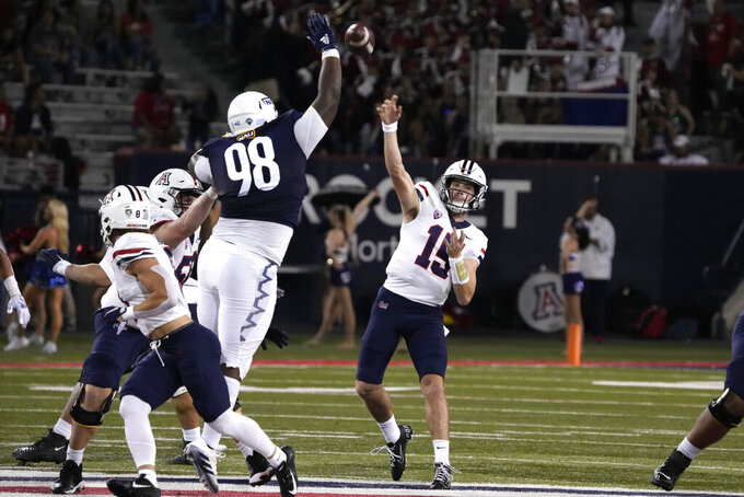 Arizona quarterback Will Plummer (15) throws for a touch down while being pressured by Northern Arizona defensive lineman Sheldon Newton (98) during the first half of an NCAA college football game, Saturday, Sept. 18, 2021, in Tucson, Ariz. (AP Photo/Rick Scuteri)