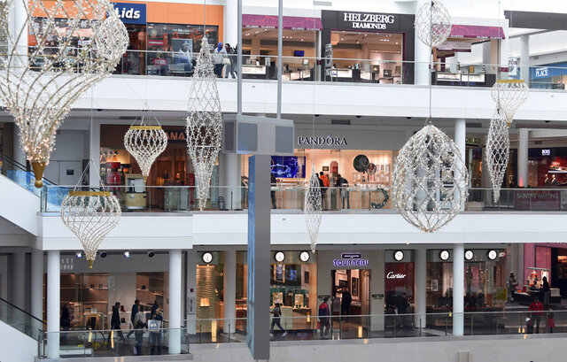 FILE - In this Dec. 22, 2017, file photo people shop at the Pentagon City Mall in Arlington, Va. Clothing retailers, particularly those in malls, have been devastated by changing consumer behavior. More than 9,000 stores were shuttered last year. (AP Photo/Susan Walsh, File)