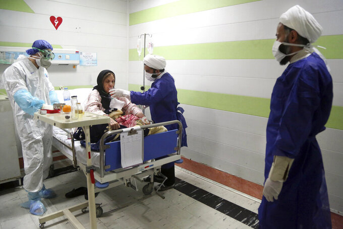 In this Saturday, March 7, 2020, a cleric, right, assists a medic treating a patient infected with the new coronavirus, at a hospital in Qom, 78 miles (125 kilometers) south of the capital Tehran, Iran. With the approaching Persian New Year, known as Nowruz, officials kept up pressure on people not to travel and to stay home. Health Ministry spokesman Kianoush Jahanpour, who gave Iran's new casualty figures Sunday, reiterated that people should not even attend funerals. (Mohammad Ali Marizad/Rasa News Agency via AP)