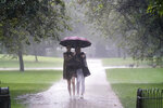 Two women walks through heavy rain in St James's Park in central London,  Sunday July 25, 2021. Thunderstorms bringing lightning and torrential rain to the south are set to continue until Monday it is forecast. (Victoria Jones/PA via AP)