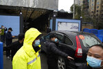 """FILE - In this file photo dated Sunday, Jan. 31, 2021, security personnel clear the way for a convoy of the World Health Organization team to enter the Huanan Seafood Market on the third day of field visit in Wuhan in central China's Hubei province. In a commentary published Wednesday Aug. 25, 2021, the international scientists dispatched to China by the World Health Organization to look for the origins of the coronavirus say the search has """"stalled"""" and warn the window is closing to conduct critical studies that could provide clues on how the virus first infected people. (AP Photo/Ng Han Guan)"""