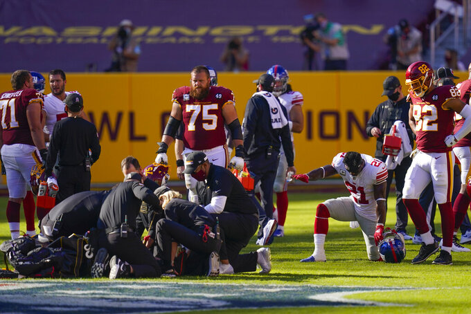 Members of the medical team huddle around Washington Football Team quarterback Kyle Allen (8) who was injured in a play against New York Giants strong safety Jabrill Peppers (21), right kneeling, in the first half of an NFL football game, Sunday, Nov. 8, 2020, in Landover, Md. (AP Photo/Patrick Semansky)