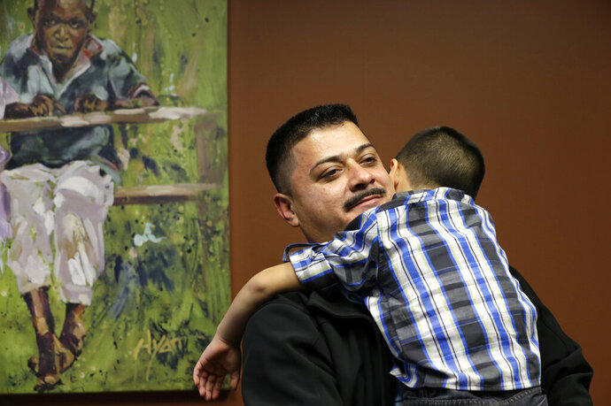 FILE - In this Friday, Oct. 17, 2014 file photo, Ignacio Lanuza-Torres holds his son, Isaiah, 4, during a portrait session in Seattle. Lanuza-Torres, a Mexican immigrant who was nearly deported after a U.S. Immigration and Customs Enforcement lawyer forged a key document in his case, accomplished a fair amount by suing over the misconduct. The lawsuit helped prompt a criminal investigation that sent the lawyer to jail, established legal precedent concerning constitutional rights during immigration proceedings, and resulted in a small settlement from the lawyer. But the case failed in its effort to hold the federal government liable for its lawyer's actions, and now the Justice Department is trying to squeeze him and his attorneys for legal fees and costs that will likely top $100,000.(AP Photo/Elaine Thompson, File)