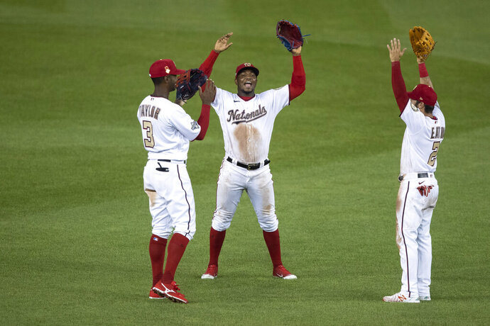 Washington Nationals left fielder Michael A. Taylor, left, center fielder Victor Robles, and left fielder Adam Eaton celebrate while socially distant after a baseball game against the New York Yankees at Nationals Park, Saturday, July 25, 2020, in Washington. (AP Photo/Alex Brandon)