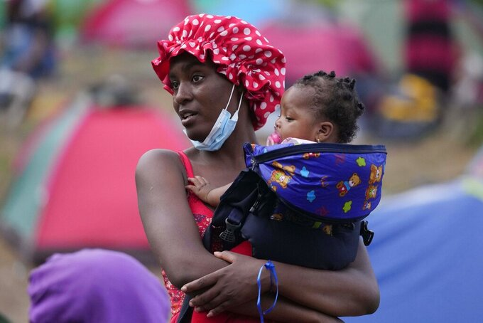 A migrant holds her daughter at a camp, in Acandi, Colombia, Tuesday, Sept. 14, 2021. The migrants, following a well-beaten, multi-nation journey towards the U.S., will continue their journey through the jungle known as the Darien Gap. (AP Photo/Fernando Vergara)
