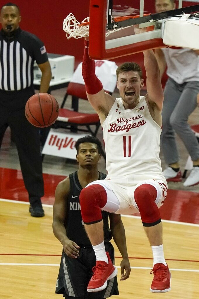 Wisconsin's Micah Potter dunks during the second half of an NCAA college basketball game against Minnesota Thursday, Dec. 31, 2020, in Madison, Wis. (AP Photo/Morry Gash)