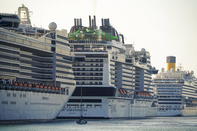 A view of the MSC Grandiosa cruise ship, center, in Civitavecchia, near Rome, Wednesday, March 31, 2021. MSC Grandiosa, the world's only cruise ship to be operating at the moment, left from Genoa on March 30 and stopped in Civitavecchia near Rome to pick up more passengers and then sail toward Naples, Cagliari, and Malta to be back in Genoa on April 6. For most of the winter, the MSC Grandiosa has been a lonely flag-bearer of the global cruise industry stalled by the pandemic, plying the Mediterranean Sea with seven-night cruises along Italy's western coast, its major islands and a stop in Malta. (AP Photo/Andrew Medichini)