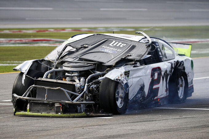 Brad Keselowski (2) drives is damaged car down pit road after a wreck during a NASCAR Cup Series auto race at Talladega Superspeedway, Monday, Oct 14, 2019, in Talladega, Ala. (AP Photo/Butch Dill)