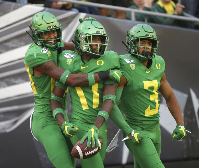 Oregon's Bryan Addison, left, Daewood Davis and Johnny Johnson III celebrate a fourth-quarter interception that Davis ran back for a touchdown against Nevada in an NCAA college football game Saturday, Sept. 7, 2019, in Eugene, Ore. (AP Photo/Chris Pietsch)