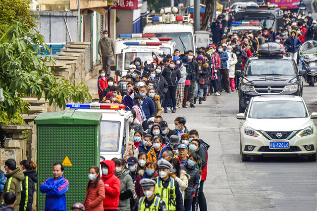 In this Jan. 29, 2020 photo, people line up to buy face masks from a medical supply company in Nanning in southern China's Guangxi Zhuang Autonomous Region. (Chinatopix via AP)