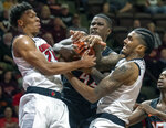 Louisville forward Dwayne Sutton, left, and Louisville center Malik Williams, right, battle Virginia Tech Hokies guard Ty Outlaw for the ball during the first half of an NCAA college basketball game Monday, Feb. 4, 2019, in Blacksburg, Va. (AP Photo/Don Petersen)