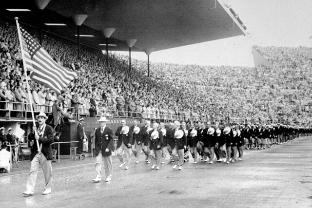 FILE - In this July 21, 1952, file photo, members of the United States Olympic team holding their hats over their hearts as they pay tribute to Finland's President Juho K. Passikivi, march into Olympic Stadium during the opening ceremonies of the Summer Olympic games in Helsinki, Finland. (United Press via AP, File)