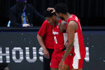 Houston guard Marcus Sasser (0) walks off the court with teammate forward Justin Gorham, right, at the end of a men's Final Four NCAA college basketball tournament semifinal game against Baylor, Saturday, April 3, 2021, at Lucas Oil Stadium in Indianapolis. Baylor won 78-59. (AP Photo/Michael Conroy)