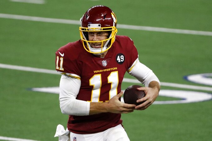 Washington Football Team quarterback Alex Smith (11) runs the ball in the second half of an NFL football game against the Dallas Cowboys in Arlington, Texas, Thursday, Nov. 26, 2020. (AP Photo/Roger Steinman)