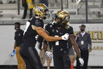Central Florida wide receiver Jaylon Robinson, right, celebrates his 10-yard touchdown on a pass play against Cincinnati with teammate wide receiver Jacob Harris during the second half of an NCAA college football game, Saturday, Nov. 21, 2020, in Orlando, Fla. (AP Photo/John Raoux)