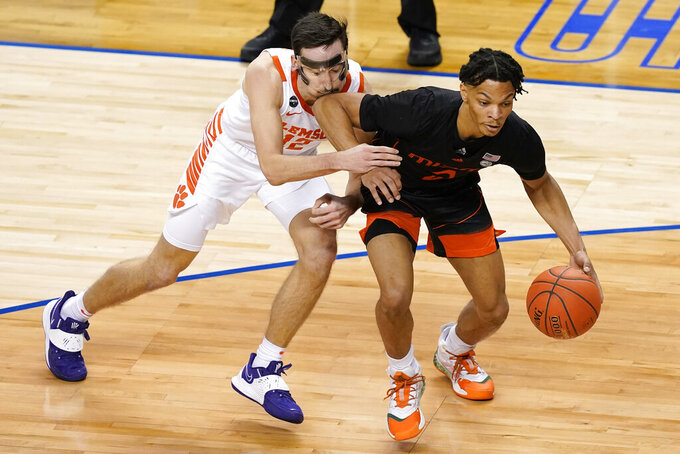Clemson guard Alex Hemenway (12) gets an elbow from Miami guard Isaiah Wong (2) during the second half of an NCAA college basketball game in the second round of the Atlantic Coast Conference tournament in Greensboro, N.C., Wednesday, March 10, 2021. (AP Photo/Gerry Broome)