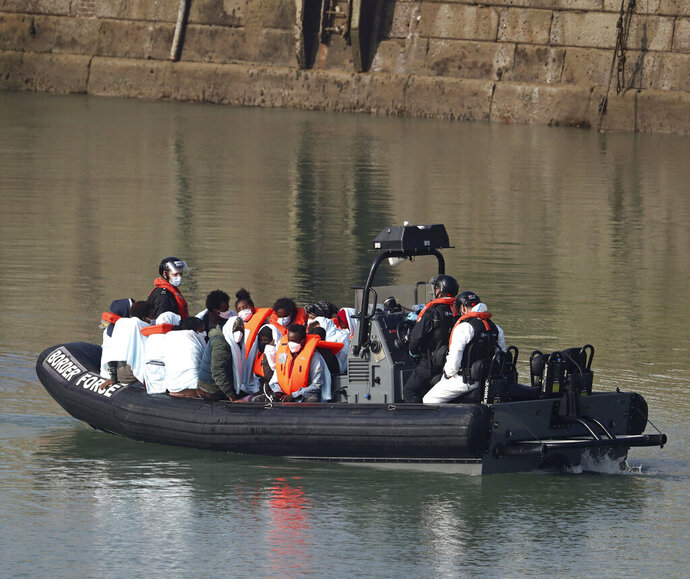 A group of people, thought to be migrants, are ferried ashore by Border Force officers, from HMC Seeker, on a Border Force rib at Dover marina in Kent, England after a small boat incident in the English Channel, Tuesday Sept. 22, 2020. (Gareth Fuller/PA via AP)