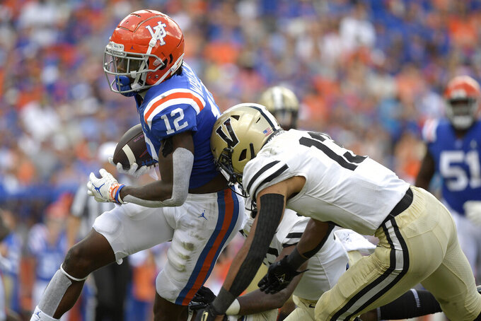 Florida wide receiver Rick Wells (12) is hit by Vanderbilt cornerback Gabe Jeudy-Lally (13) and defensive back De'Rickey Wright, rear, after catching a pass during the second half of an NCAA college football game, Saturday, Oct. 9, 2021, in Gainesville, Fla. (AP Photo/Phelan M. Ebenhack)