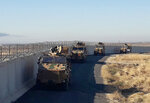 Turkish army armoured vehicles arrive near the Turkish town of Idil at the Turkey-Syria border before Turkish and Russian troops conduct their third joint patrols in northeast Syria, Friday, Nov. 8, 2019. Turkish and Russian troops are conducting joint patrols under a deal between the two countries that forced Syrian Kurdish fighters to withdraw from areas bordering Turkey. (Turkish Defence Ministry via AP, Pool)