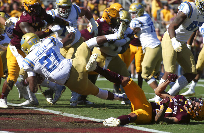 UCLA running back Joshua Kelley (27) dives into the end zone over Arizona State defensive back Chase Lucas (24) for a touchdown during the first half of an NCAA college football game, Saturday, Nov. 10, 2018, in Tempe, Ariz. (AP Photo/Ralph Freso)