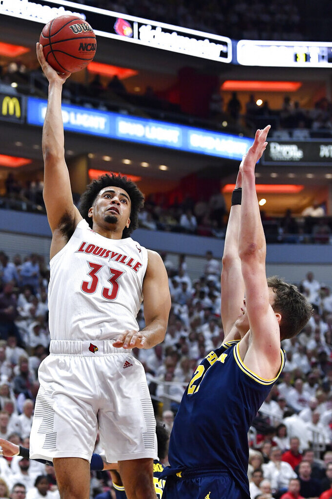 Louisville forward Jordan Nwora (33) shoots over the defense of Michigan guard Franz Wagner (21) during the second half of an NCAA college basketball game in Louisville, Ky., Tuesday, Dec. 3, 2019. Louisville won 58-43. (AP Photo/Timothy D. Easley)