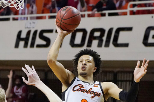 FILE - Oklahoma State guard Cade Cunningham (2) shoots against Arkansas in the second half of an NCAA college basketball game in Stillwater, Okla., in this Saturday, Jan. 30, 2021, file photo. Cade Cunningham has announced he will enter the NBA draft after a dynamic freshman season that saw him named a first-team AP All-American. (AP Photo/Sue Ogrocki, File)