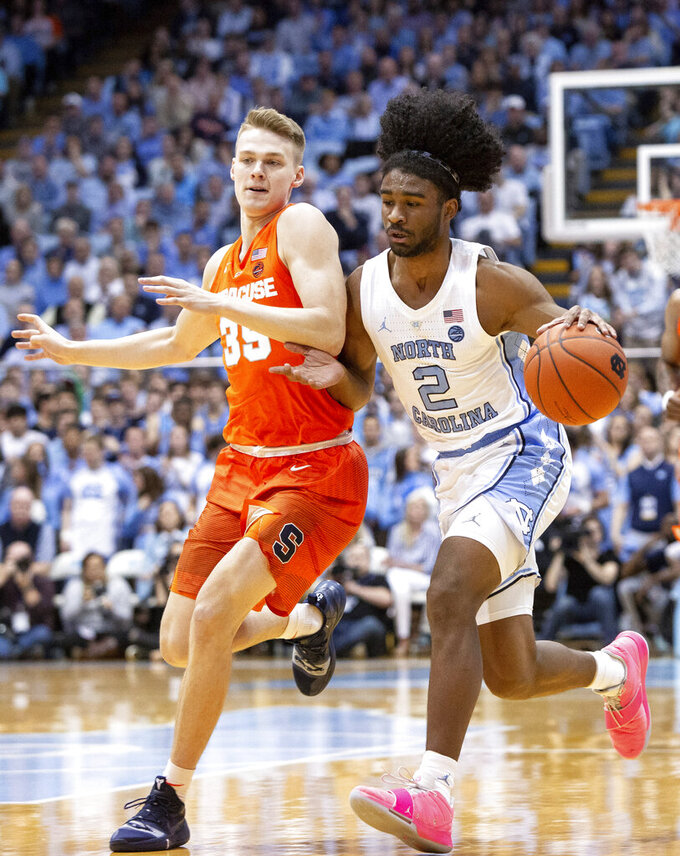CORRECTS TO COBY WHITE AND NOT COLBY AS ORIGINALLY SENT - North Carolina's Coby White (2) handles the ball as Syracuse's Buddy Boeheim (35) defends during the first half of an NCAA college basketball game in Chapel Hill, N.C., Tuesday, Feb. 26, 2019. (AP Photo/Ben McKeown)