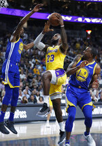 Los Angeles Lakers forward LeBron James (23) shoots between Golden State Warriors forward Kevin Durant, left, and guard Andre Iguodala during the first half of an NBA preseason basketball game Wednesday, Oct. 10, 2018, in Las Vegas. (AP Photo/John Locher)