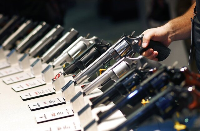 FILE - In this Jan. 19, 2016 file photo, handguns are displayed at the Shooting, Hunting and Outdoor Trade Show in Las Vegas. Leaders of a conservative advocacy group want quick action from a Nevada judge to block enactment of a statewide