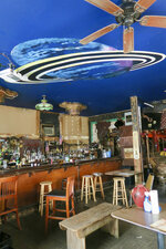 A planetary painting on the ceiling of Saturn Bar, and blank spaces on the wall where paintings by Mike Frolich were long displayed. The bar changed hands in 2021 and the Frolich paintings were retained by the former owners. (Ian McNulty/The Times-Picayune/The New Orleans Advocate via AP)