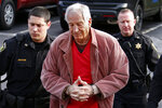 FILE - In this Oct. 29, 2015 file photo Former Penn State University assistant football coach Jerry Sandusky, center, arrives at the Centre County Courthouse for a hearing about his appeal on his child sex-abuse conviction, in Bellefonte, Pa. Penn State stands to collect hundreds of thousands of dollars from the defunct charity for children founded by Sandusky to settle claims that were never fleshed out in a civil lawsuit. (AP Photo/Gene J. Puskar, File)