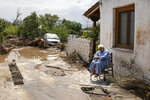 A woman sits outside her home following a storm at the village of Politika, on Evia island, northeast of Athens, on Sunday, Aug. 9, 2020. Five people have been found dead and dozens have been trapped in their homes and cars from a storm that has hit the island of Evia, in central Greece, police say. (AP Photo/Yorgos Karahalis)