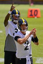 Pittsburgh Steelers quarterbacks Dwayne Haskins (3) and Mason Rudolph work during the team's NFL minicamp football practice in Pittsburgh, Thursday, June 17, 2021. (AP Photo/Gene J. Puskar)