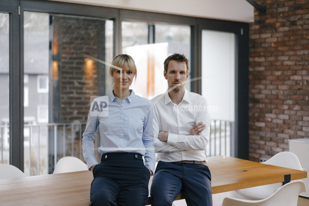 Successful businessman and woman standing in office, with arms crossed