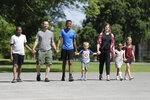 Paul and Cindy Neal walk with their children, from left, Musse, Belachew, Elisha, Edile and Miriam at Garfield Park, Sunday, June 14, 2020, in Indianapolis. The Associated Press discussed race with six white couples who have adopted or have custody of Black children. These parents are trying to help their children understand race in America while getting an accelerated course themselves. (AP Photo/Darron Cummings)