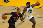 Toronto Raptors guard Norman Powell (24) dribbles against Golden State Warriors forward Eric Paschall (7) during the first half of an NBA basketball game in San Francisco, Sunday, Jan. 10, 2021. (AP Photo/Jeff Chiu)
