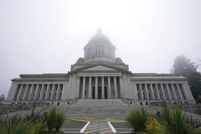 """FILE - In this Jan. 7, 2021, file photo, the Legislative Building is shown partially shrouded in fog at the Capitol in Olympia, Wash. Washington state's richest residents, including Bill Gates and Jeff Bezos, would pay a wealth tax on certain financial assets worth more than $1 billion under a proposed bill whose sponsor says she is seeking a fair and equitable tax code. Under the bill, starting Jan. 1, 2022, for taxes due in 2023, a 1% tax would be levied not on income, but on """"extraordinary"""" assets ranging from cash, publicly traded options, futures contracts, and stocks and bonds. (AP Photo/Ted S. Warren, File)"""