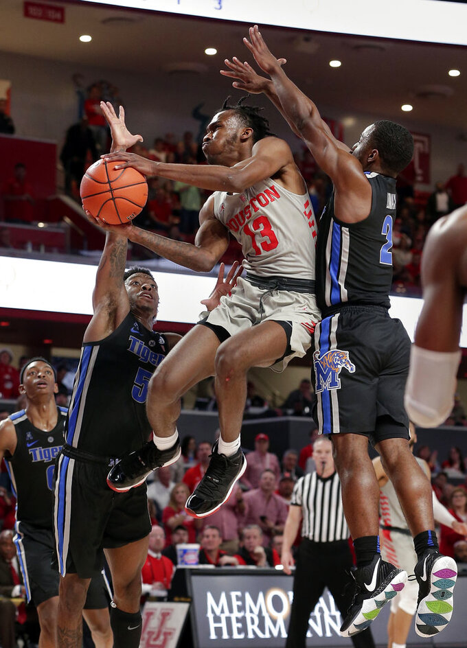 Houston guard Dejon Jarreau (13) puts up a shot between Memphis guard Kareem Brewton Jr. (5) and guard Alex Lomax (2) during the second half of an NCAA college basketball game Sunday, Jan. 6, 2019, in Houston. (AP Photo/Michael Wyke)