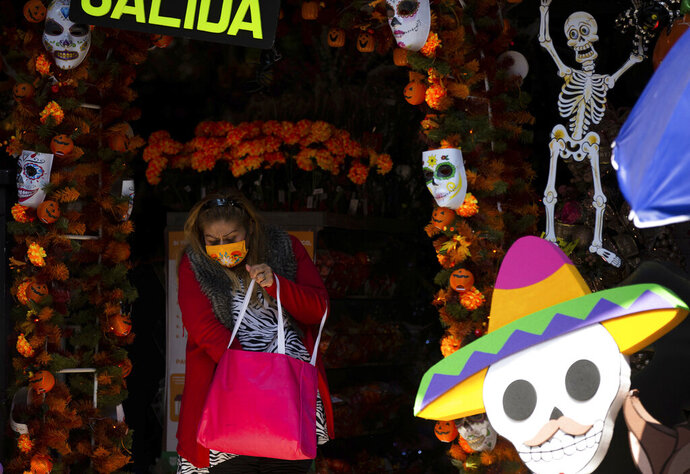 A shopper leaves a Day of the Dead souvenirs store in Mexico City, Friday, Oct. 30, 2020. Prior to the coronavirus pandemic, Mexico's economy was in recession, and that only deepened with the economic shutdown provoked by measures aimed at slowing the spread of COVID-19 during the second quarter. (AP Photo/Fernando Llano)