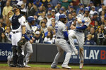 Los Angeles Dodgers' Yasiel Puig (66) celebrates with Cody Bellinger (35) and Max Muncy (13) after hitting a three-run home run during the sixth inning of Game 7 of the National League Championship Series baseball game against the Milwaukee Brewers Saturday, Oct. 20, 2018, in Milwaukee. (AP Photo/Jeff Roberson)
