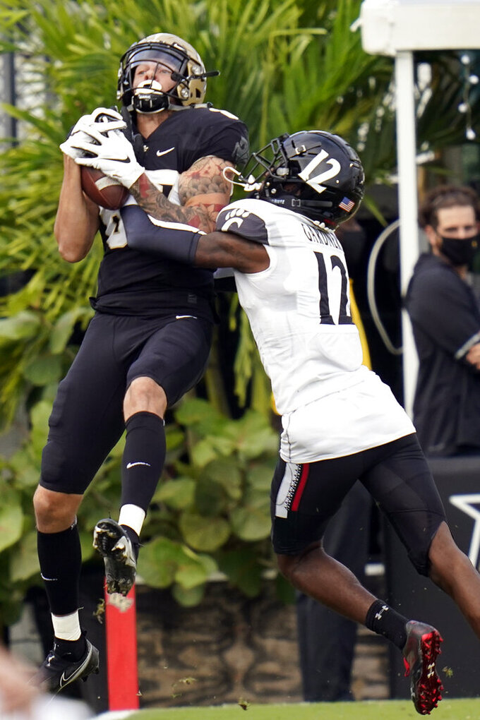 Central Florida wide receiver Jacob Harris, left, makes a reception in front of Cincinnati cornerback Ahmad Gardner (12) to the 3-yard line during the first half of an NCAA college football game, Saturday, Nov. 21, 2020, in Orlando, Fla. (AP Photo/John Raoux)
