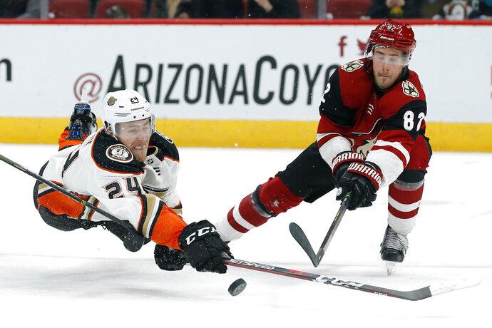 Anaheim Ducks center Carter Rowney (24) shoots in front of Arizona Coyotes defenseman Jordan Oesterle during the third period during an NHL hockey game Thursday, March 14, 2019, in Glendale, Ariz. Arizona defeated Anaheim 6-1. (AP Photo/Rick Scuteri)