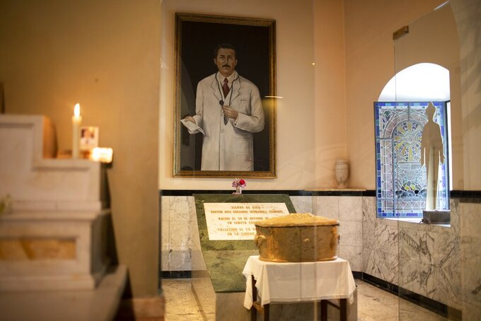"""The remains of Venezuelan Dr. Jose Gregorio Hernandez popularly known as the """"doctor of the poor"""", sit in an urn backdropped by his portrait, inside the Nuestra Senora de la Candelaria Catholic church, in Caracas, Venezuela, Friday, April 23, 2021. Hernandez is set to be beatified by the Catholic church, a step towards sainthood, on April 30th in the Venezuelan capital.  (AP Photo/Ariana Cubillos)"""