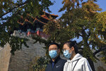 A couple wearing face masks to help curb the spread of the coronavirus walk by the Turret of the Forbidden City in Beijing, Sunday, Oct. 25, 2020. With the outbreak of COVID-19 largely under control within China's borders, the routines of normal daily life have begun to return for its citizens. (AP Photo/Andy Wong)