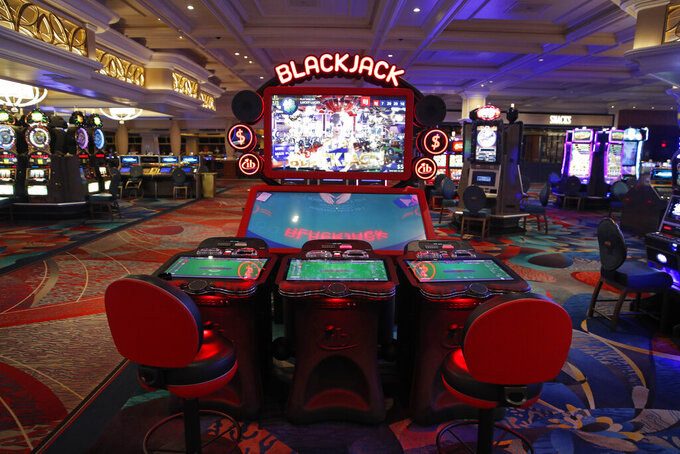 Chairs are removed to keep social distancing between players as a coronavirus safety precaution at an electronic gaming machine in the closed Bellagio hotel and casino, Wednesday, May 20, 2020, in Las Vegas. Casino operators in Las Vegas are awaiting word when they will be able to reopen after a shutdown during the coronavirus outbreak. (AP Photo/John Locher)