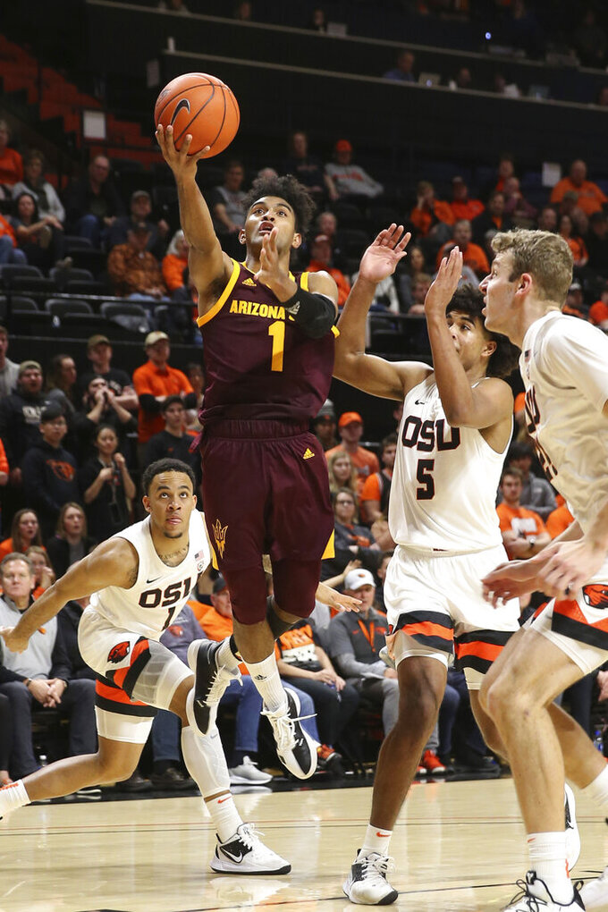 Arizona State's Remy Martin, center, shoots between against Oregon State's Sean Miller-Moore, left, Ethan Thompson, center right, and Kylor Kelley, right, during the second half of an NCAA college basketball game in Corvallis, Ore., Thursday, Jan. 9, 2020. (AP Photo/Chris Pietsch)