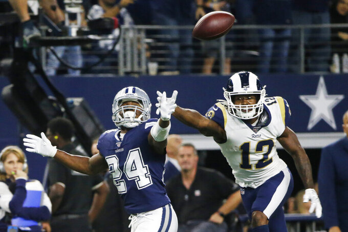 Dallas Cowboys cornerback Chidobe Awuzie (24) and Los Angeles Rams wide receiver Brandin Cooks (12) reach for the ball in the second half of an NFL football game in Arlington, Texas, Sunday, Dec. 15, 2019. (AP Photo/Michael Ainsworth)
