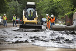 A crew using hand tools and a bobcat work to clear streets after flash flooding in Flagstaff, Ariz., on Wednesday, July 14, 2021. The threat of flash flooding will remain through next week, the National Weather Service said, though the coverage will be more scattered than widespread. (Jake Bacon/Arizona Daily Sun via AP)