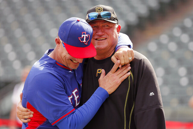 FILE - In this May 27, 2016, file photo, Texas Rangers manager Jeff Banister, left, and Pittsburgh Pirates manager Clint Hurdle greet each other during batting practice before a baseball game in Arlington, Texas. Clint Hurdle began sending his daily notes of inspiration more than 10 years ago, during his days managing the Colorado Rockies. They were a simple, small way of checking in with everybody on his staff to discuss leadership ideas or offer support. (AP Photo/Tony Gutierrez, File)